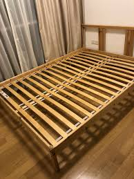 A wooden bed without mattress yet