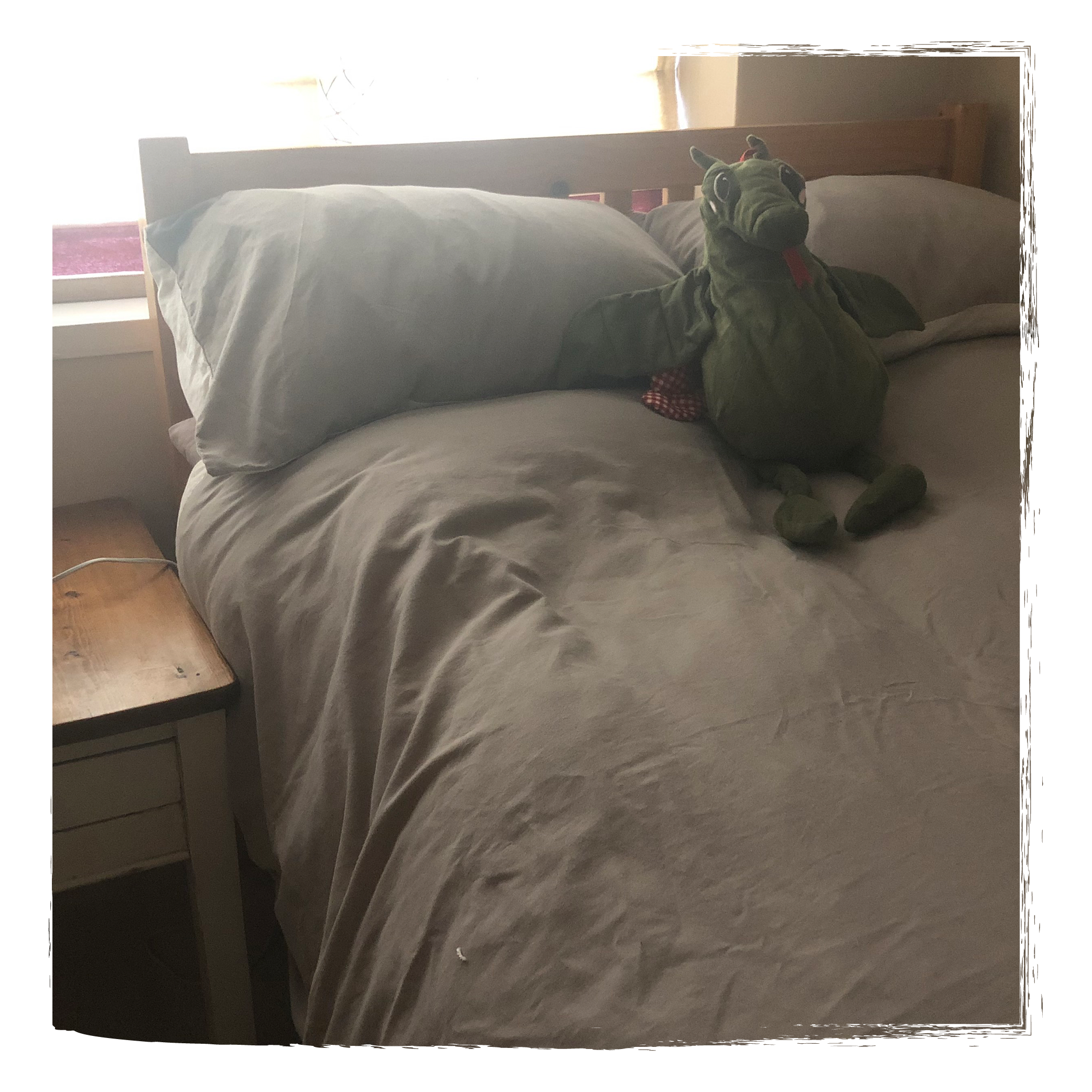 a bed with a dragon stuffed toy